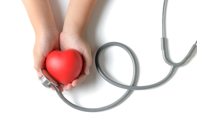 Child hands holding red heart with stethoscope isolated
