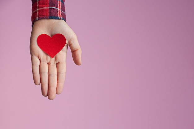 Child hands holding red paper heart in hands on pink background. valentines day, mothers day and love concepts.