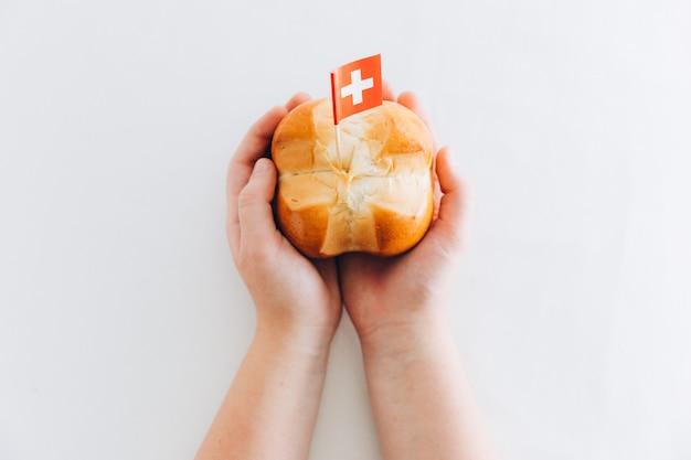 スイスの国民の祝日を祝うために十字形の伝統的なパンを持っている子供の手