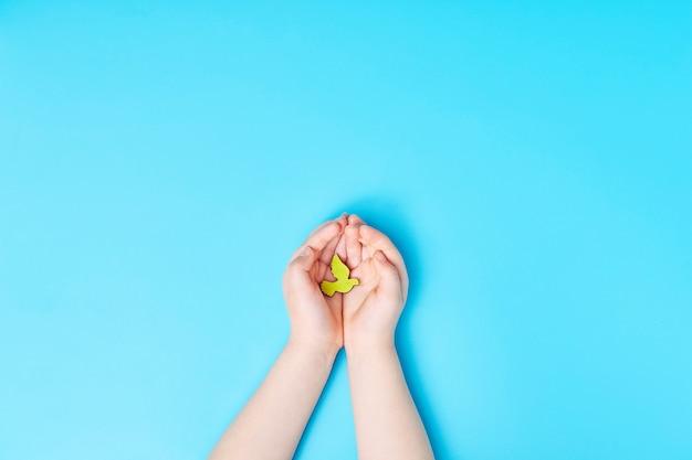 青の背景に黄色い鳩の鳥を持つ子どもの手、国際平和デー、世界平和デーのコンセプト。