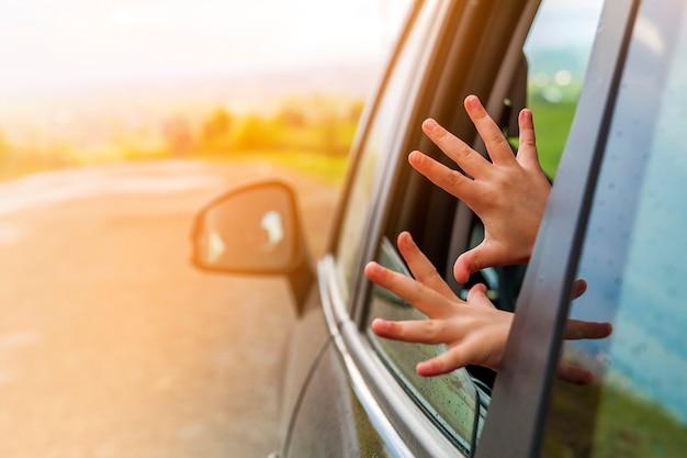 子供は休暇への旅行中に車の窓に手を渡します。柔らかな光の効果。