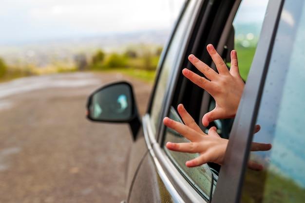 休暇への旅行中に車の窓に子供手