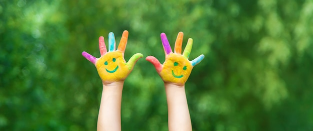 Руки ребенка в красках улыбкой.