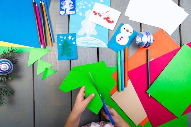 Child hands make handmade christmas toys from cardboard children's diy concept