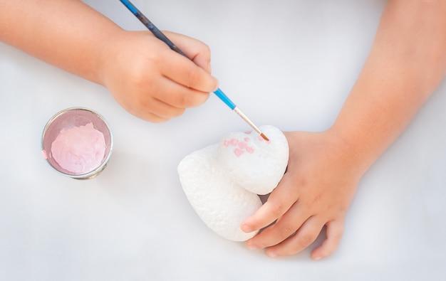 아이 손에 분홍색 페인트와 브러시로 마음을 페인트