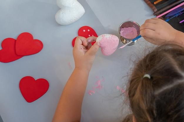 子供の手はピンクのペンキとブラシでハートをペイントします