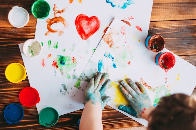 A child hands painting colorful mosaic the kid is drawing on white sheets with finger paints