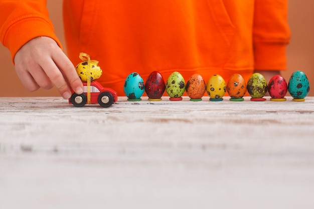 Child hands playing easter egg on car on orange background. happy easter concept.