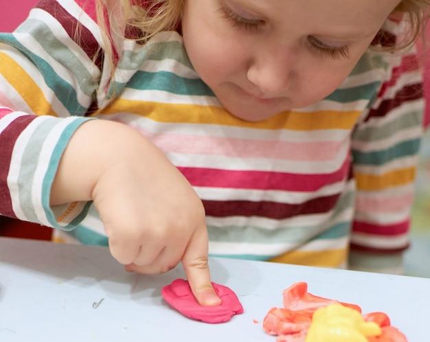 カラフルな粘土で遊ぶ子供の手。塑像用粘土。生地を再生する、社会的距離検疫covid-19、自己隔離、オンライン教育の概念、ホームスクーリング。家にいる幼児の女の子、幼稚園は閉園しました。