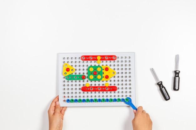 흰색 테이블 배경에 장난감 도구를 가지고 노는 아이 손. 평면도