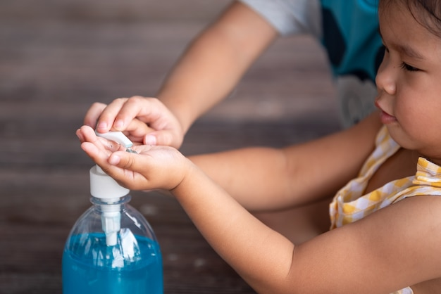 Child hands using wash hand sanitizer gel pump dispenser