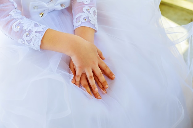 Child hands white dress