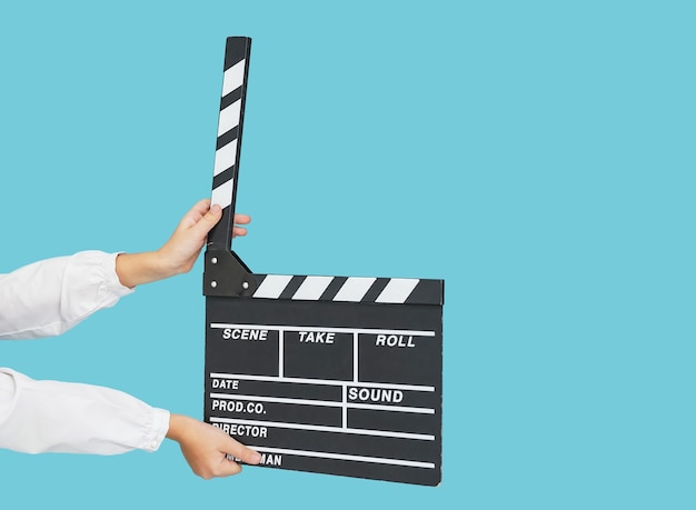Child hands with empty black filmmaking clapperboard