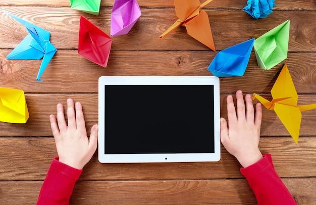 Руки ребенка с планшета и оригами из цветной бумаги на деревянном столе