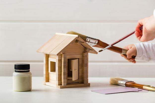 장난감 목조 주택 및 페인트 브러시 홈 서비스 개념으로 아이 손 프리미엄 사진