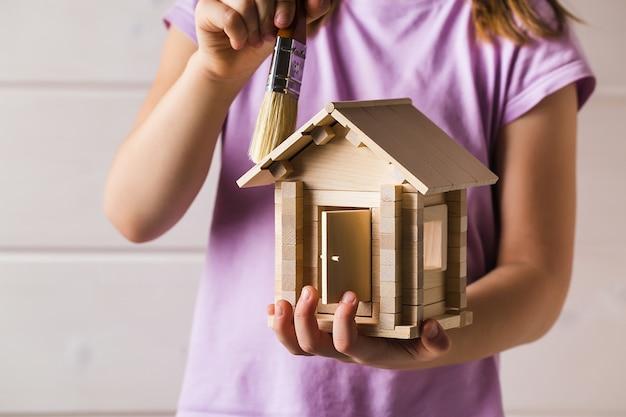 장난감 목조 주택 및 페인트 브러시 홈 서비스 개념으로 아이 손