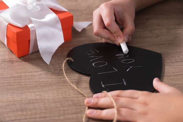 Child hands writes i love you on chalk board in form of heart.