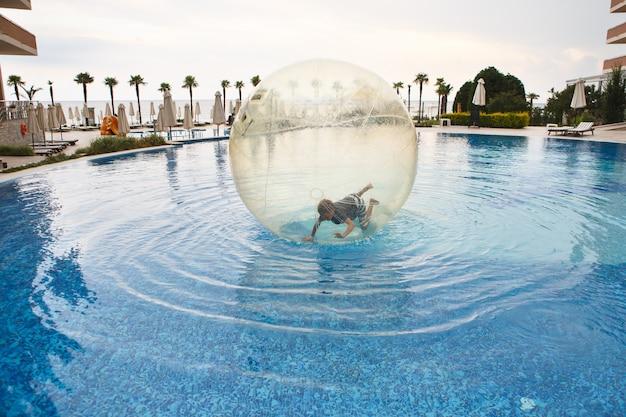 子供は夏のリゾートのプールの水にある大きなプラスチックの風船の中で楽しんでいます。大きく膨らませて透明なボールの中の小さな男の子が走って楽しんでいます。