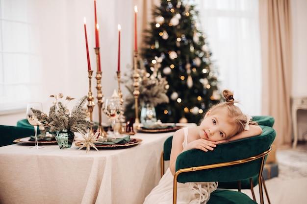 お祝いのテーブルで退屈な食事中に席を持っている子供