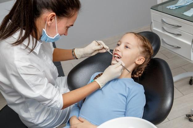 Ребенок, имеющий стоматологическое обследование у специалиста в офисе стоматолога