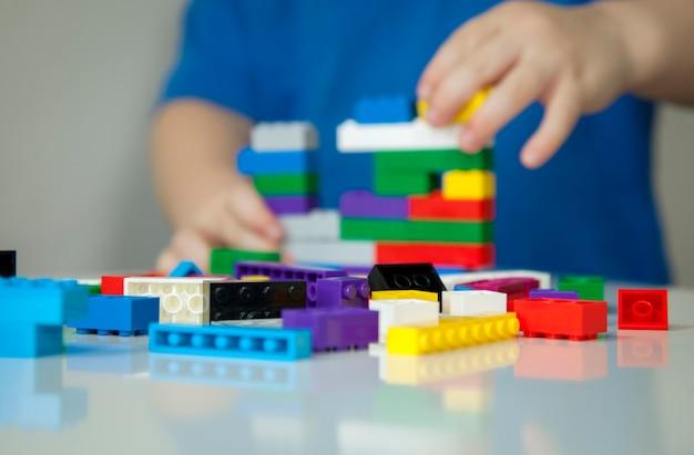 楽しんで、明るいレンガで構築している子供。
