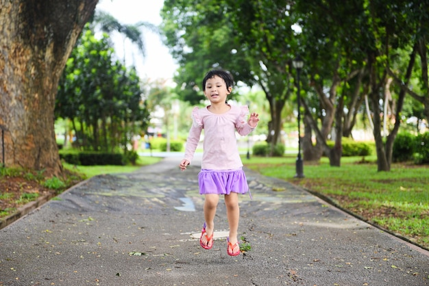 Child having fun playing outside asian kid girl happy jumping in the park garden international children's day