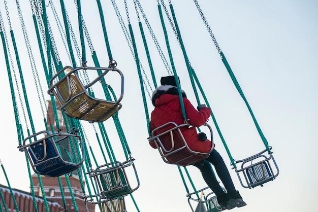 Ребенок весело езда на цепной карусели в парке развлечений b