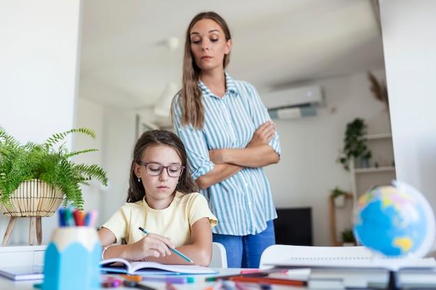 宿題をしながら集中力に問題がある子供。ストレスのたまった母と娘は、宿題の失敗、学校の問題に不満を感じていました。母は難しい宿題で娘を助けます