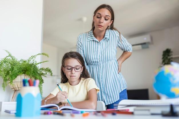 숙제를 하는 동안 집중력에 문제가 있는 아이. 숙제 실패, 학교 문제로 인해 스트레스를 받은 엄마와 딸. 어머니는 어려운 숙제로 그녀의 딸을 도우십시오