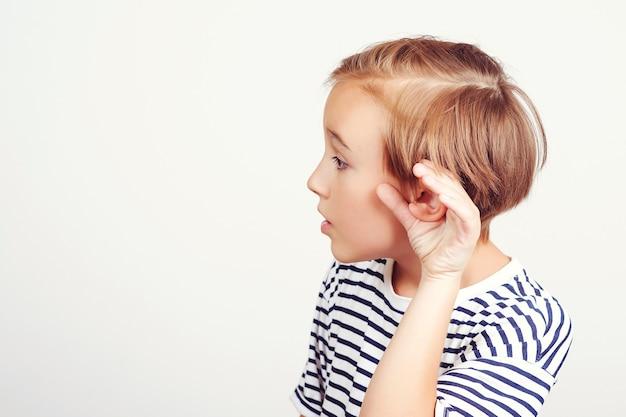 흰색 배경 위에 자식 청력 험담입니다. 뭔가 듣고, 귀에 손을 제스처를 듣고 학교 소년. 재미있는 아이는 주의 깊게 듣는다. 아이와 가족 커뮤니케이션입니다. 부모의 말을 들으십시오. 귀여운 소년은 귀 근처에 손을 잡고 있습니다.