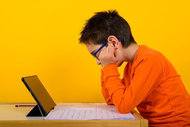 아이가 노란색으로 학교 선생님과 함께 원격 수업을 듣는다. 프리미엄 사진