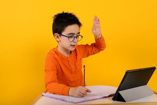 Ребенок слышит удаленный урок со школьным учителем на желтом