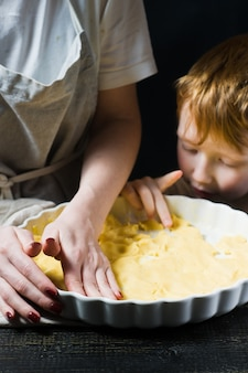 The child helps her mother to cook a cake, cooking.