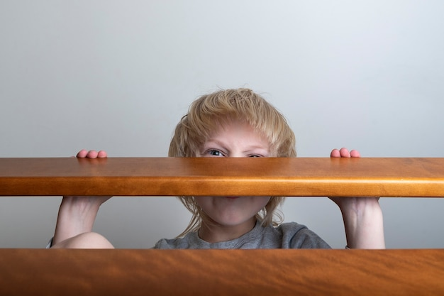 Child hides behind the railing. violence in family. domestic violence. abuse