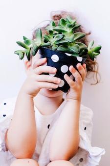 Child hiding face behind pot