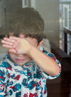 Child hiding face with hand behind glass
