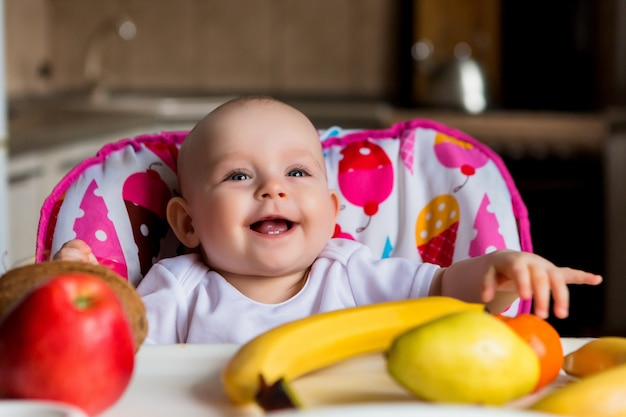 Child in a high chair eating fruit and smiling