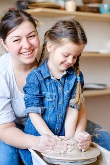 Детское хобби. творческий гончарный досуг. художественное воспитание ребенка. маленькая девочка и мастер гончара работают с глиной