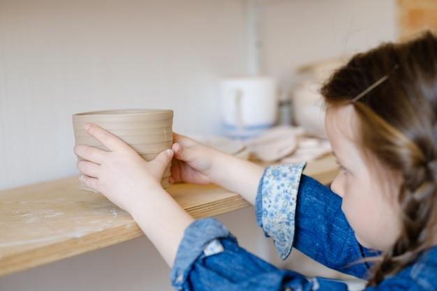 Детское хобби. творческий гончарный досуг. художественное воспитание ребенка. маленькая девочка кладет на полку глиняный кувшин ручной работы