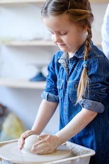 Детское хобби. творческий гончарный досуг. художественное воспитание ребенка. маленькая девочка работает с глиной