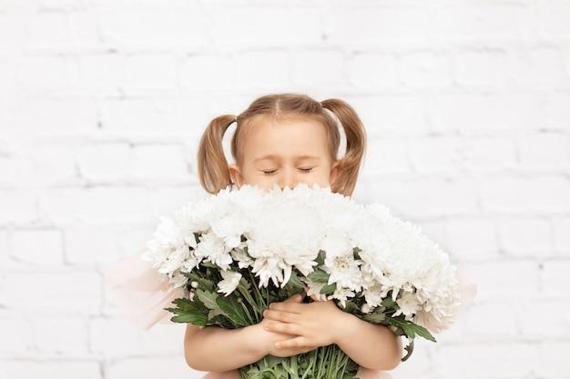 子供は先生の母の誕生日の白いスタジオギフトに分離された花束の花を保持しますアレルギーなし