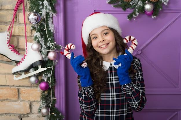 Ребенок держит рождественскую конфету. полосатая конфета традиционные зимние праздники. элегантный счастливый ребенок в шляпе и перчатках. в ожидании деда мороза. рождественский декор. конфеты из перечной мяты. идеи украшения.