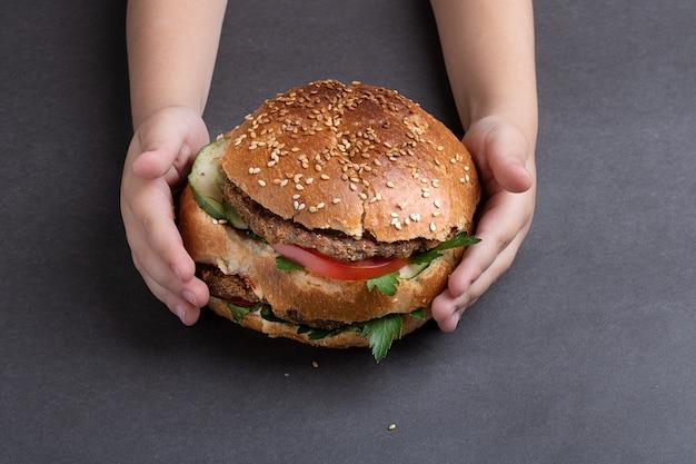 灰色のテーブルでハンバーガーを抱いた子供。上からの眺め
