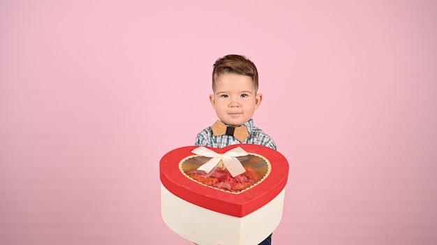 Ребенок держит подарочную коробку в форме сердца. фото высокого качества