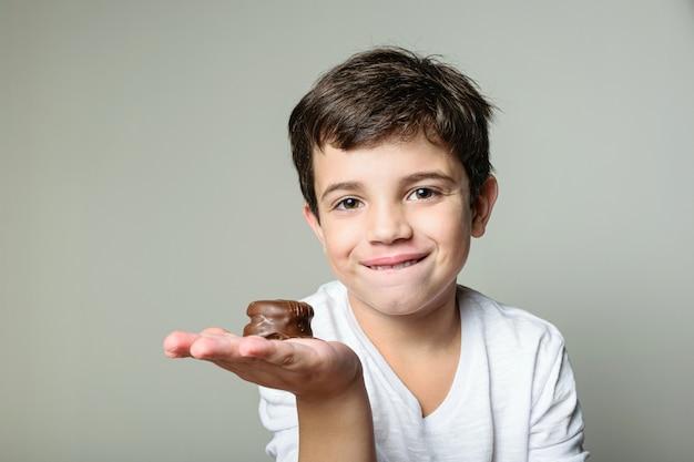 Ребенок держит в руке мини-бразильский медовый торт