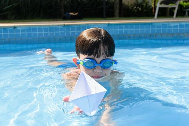 Ребенок держит бумажный кораблик в бассейне в летний день.