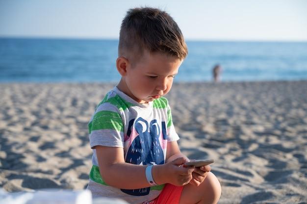 ビーチに座っている間石を保持している子供。