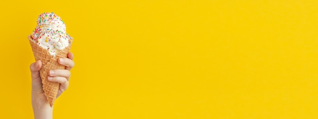 カラフルなスプリンクル、クローズアップで飾られた明るい黄色と青の甘いデザートにバニラアイスクリームコーンを保持している子供