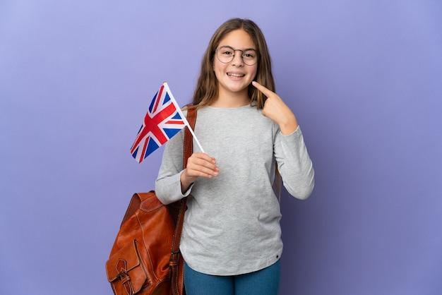 Ребенок держит флаг соединенного королевства на изолированном фоне, показывая жест пальца вверх