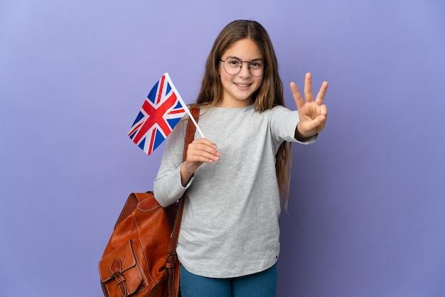 幸せな孤立した背景の上にイギリスの旗を保持し、指で3を数える子供